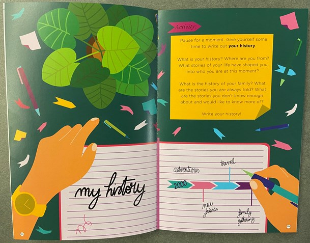 """This Book is Anti-Racist"" by Tiffany Jewel is open to a full spread opened to an illustration by Aurelia Durand showing an image of a desk with a person's hands holding a pen and notebook and following directions and prompts listed there for the reader to explore and reflect on their personal history."